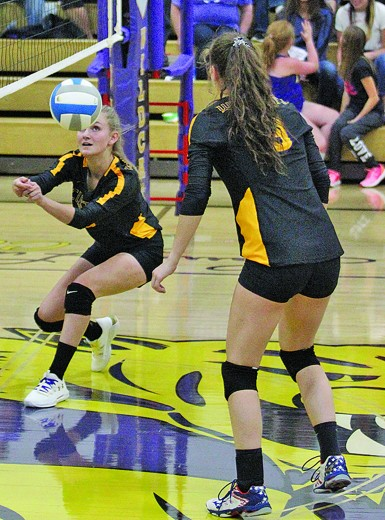 Senior setter Emily Meyer gives the ball a bump at the net in the game against Spearfish Thursday night at the Armory. At right is fellow senior Heidi Moore.