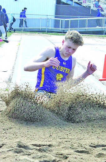 Gage Tennyson splashes into the sand following a record-breaking long jump attempt at the Custer Invitational last Thursday. Tennyson's jump of 21-5 1/4 broke a school record that had stood for 49 years