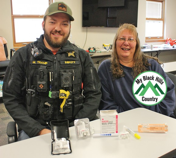 Custer school resource officer Deputy Matt Tramp, left, and Custer EMT Hapsey Nutley display the opioid antagonist products they have available to treat an overdose of opiods like heroin, oxycodone or fentynal. The black box on the left contains a single dose of Narcan which can revive a person who has stopped breathing due to an opioid overdose. Every Custer County deputy carries Narcan in his county-issued vest.